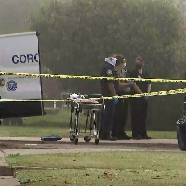 A coroner's van arrives in Willowbrook on Oct. 16, 2020. Two shooting victims were found dead after a car crash the night before. (KTLA)