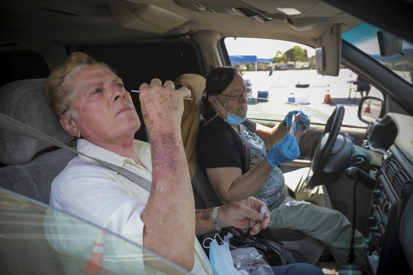 Daniel Mendoza, left, and Linda Mendoza take COVID-19 tests at a drive-in site established by the city of Santa Ana.(Irfan Khan / Los Angeles Times)
