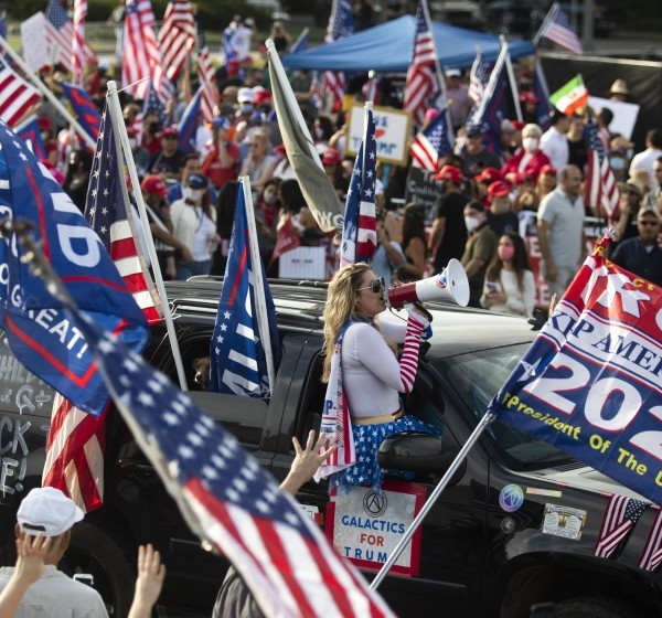 "A large crowd chants ""four more years"" during a Pro Trump rally on Santa America Blvd and Beverly Blvd in Beverly Hills on Oct. 31, 2020. (Francine Orr / Los Angeles Times)"