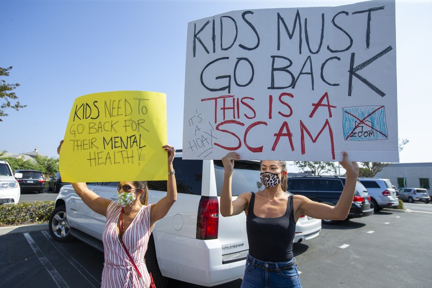 Julia Graham, left, and Karla Rivera hold signs in protest outside of the Newport-Mesa Unified School District offices in Costa Mesa on Oct. 8, 2020. (Scott Smeltzer/ Times Community News)