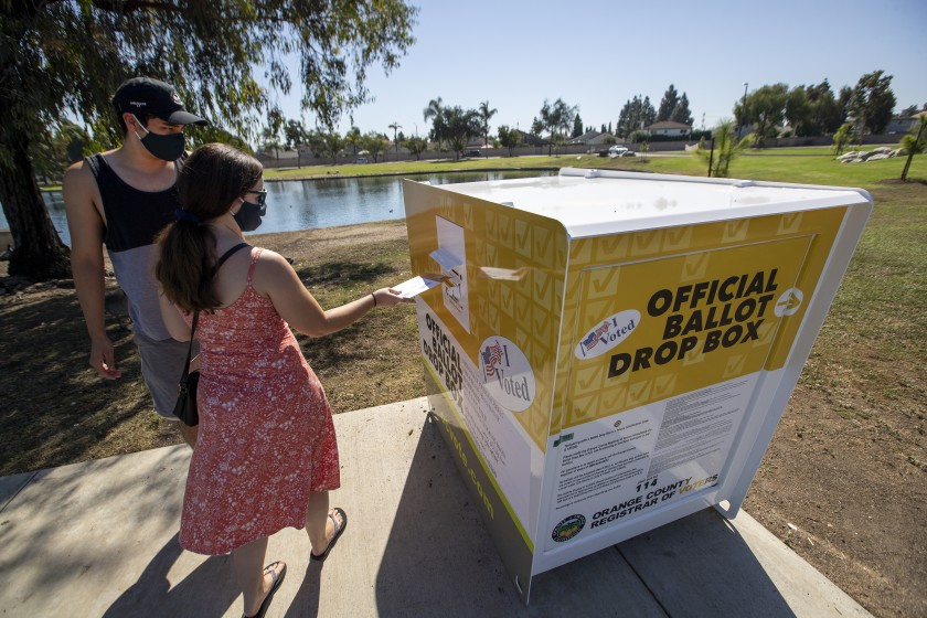 Voters place their ballots inside an official drop box at Carl Thornton Park in Santa Ana.(Allen J. Schaben / Los Angeles Times)
