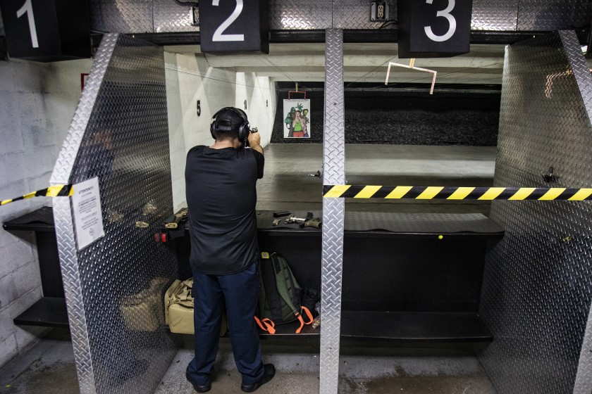 Freddy Torres of Buena Park shoots his gun at the Riverside Indoor Shooting Range in March, after the start of COVID-19 pandemic. (Gina Ferazzi / Los Angeles Times)