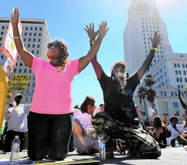 Demonstrators drop to their knees during a march in downtown L.A. in August as they protested police killings around the country.(Wally Skalij / Los Angeles Times)