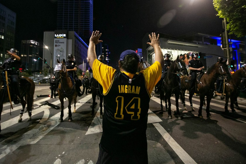 Los Angeles police officers clear the area near L.A. Live after declaring an unlawful assembly downtown following the Lakers' championship win on Oct. 11, 2020.(Jason Armond / Los Angeles Times)