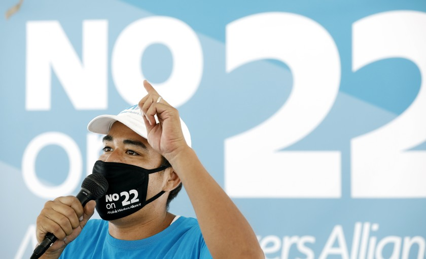 Felipe Caceres of Mobile Workers Alliance speaks at a news conference in Los Angeles against Proposition 22, the November ballot measure that would classify app-based drivers as independent contractors, exempting them from AB 5.(Christina House / Los Angeles Times)