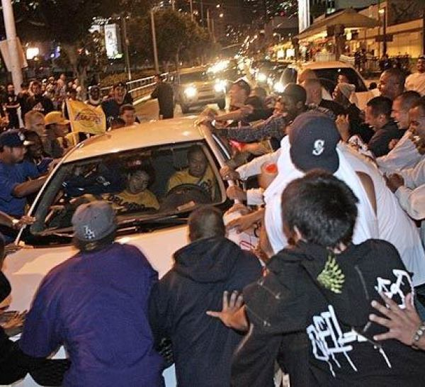 A group of people rock a car on Pico Boulevard amid celebrations of the Lakers title victory. (Gina Ferazzi / Los Angeles Times)