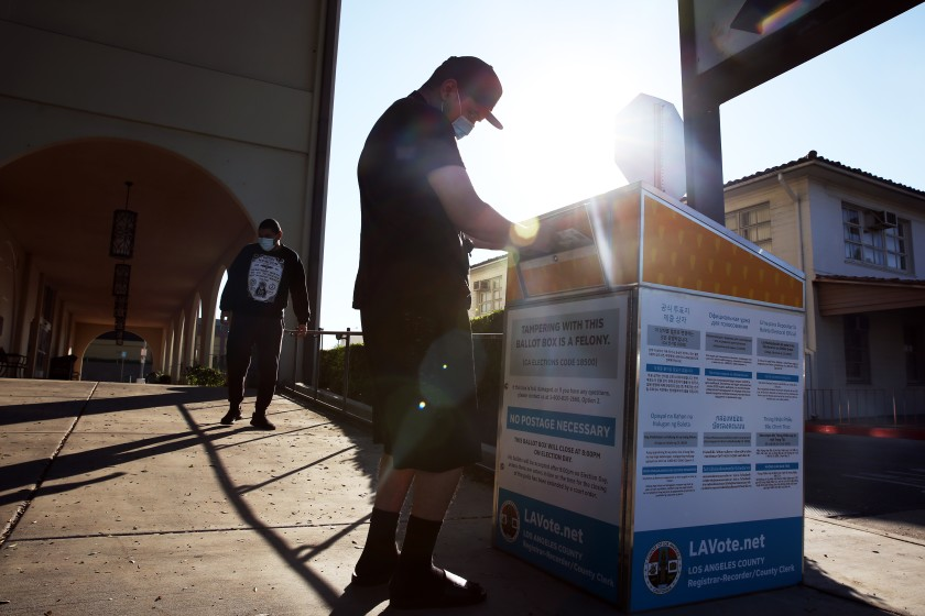 Jonathan Franco casts his vote with brother Christian Franco, left, at the Huntington Park Library ballot drop box in Huntington Park on Oct. 29, 2020. (Dania Maxwell / Los Angeles Times)