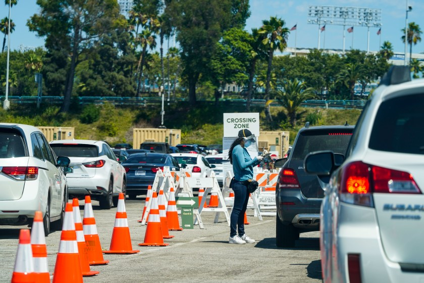 Cars line up at a COVID-19 test site at Dodger Stadium on Aug. 12 in Los Angeles.(Kent Nishimura / Los Angeles Times)
