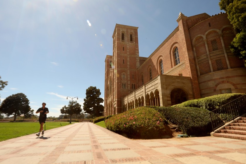 A lone jogger runs past Royce Hall on a nearly empty UCLA campus in Los Angeles on Aug. 13. (Genaro Molina/Los Angeles Times)
