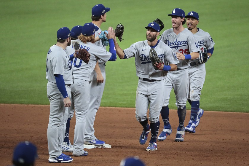 Dodgers players Chris Taylor, Cody Bellinger and Mookie Betts celebrate with teammates after their 12-3 win over the Padres in the NLDS on Oct. 8, 2020. (Robert Gauthier / Los Angeles Times)