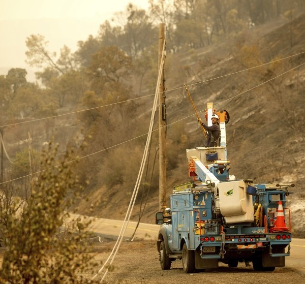 A Pacific Gas & Electric Co. worker clears a power line blocking a roadway in unincorporated Napa County on Aug. 20. PG&E is preparing for potential power shutoffs this week.(Noah Berger / Associated Press)