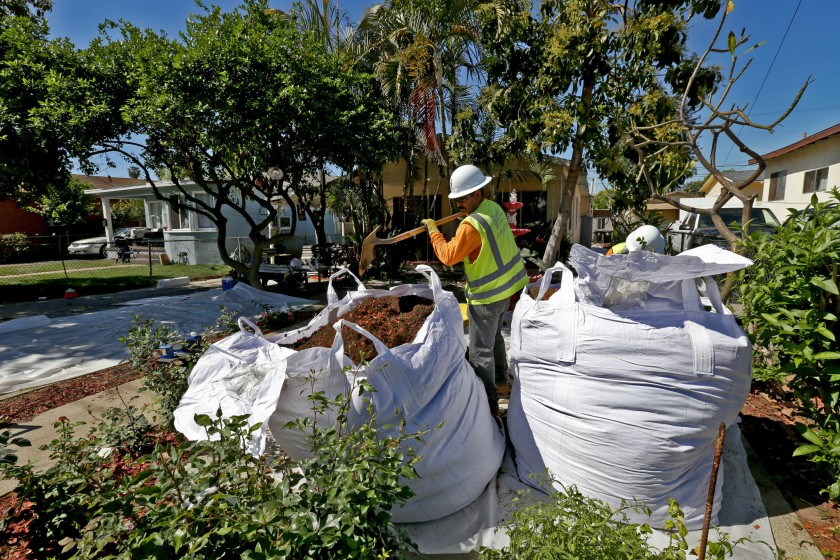 Workers remove topsoil from homes in Boyle Heights in 2015 as part of a state-led cleanup of lead contamination from thousands of properties surrounding the closed Exide Technologies battery recycling plant in Vernon.(Irfan Khan/Los Angeles Times)