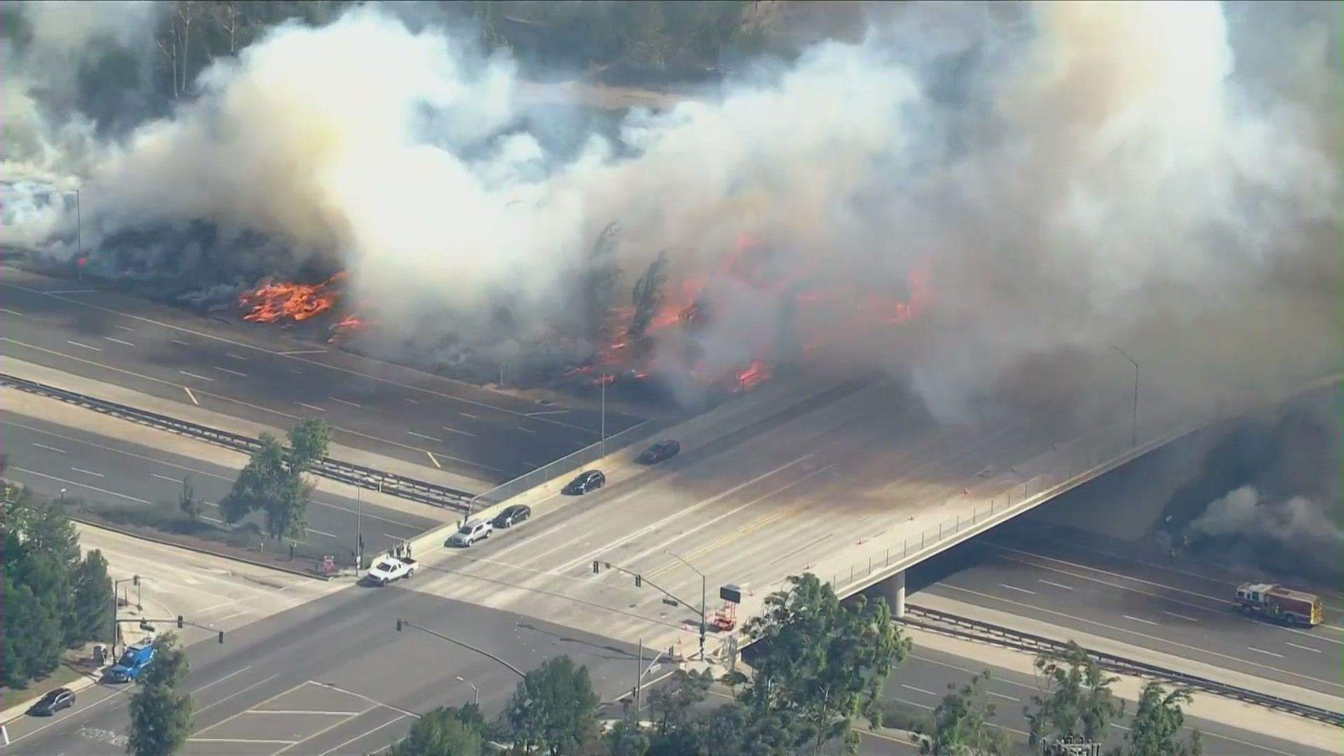 Flames rage near the Irvine Boulevard overpass above the 133 in Irvine as the Silverado Fire burns on Oct. 26, 2020. (KTLA)