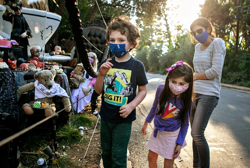 A family wears face coverings on Oct. 28, 2020 while visiting a Brentwood home that goes all out with Hollywood-caliber Halloween decorations. (Jason Armond / Los Angeles Times)