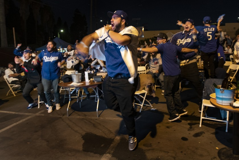 Jeff Gomez celebrates with other Dodger fans as Mookie Betts scores the go-ahead run in the sixth inning in Game 6 of the World Series, which they were watching in the parking lot of Club Bahia near Dodger Stadium on Tuesday night.(Gina Ferazzi / Los Angeles Times)
