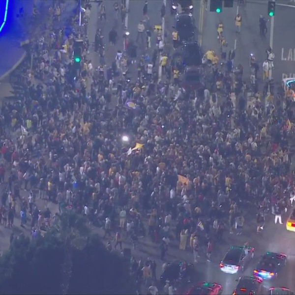 Lakers fans crowd an intersection just outside Staples Center in downtown Los Angeles, on Oct. 11, 2020, following the L.A. team's 106-93 win over the Miami Heat in the Finals. It's the team's first title since 2010, when Kobe Bryant led the team to victory. (KTLA)
