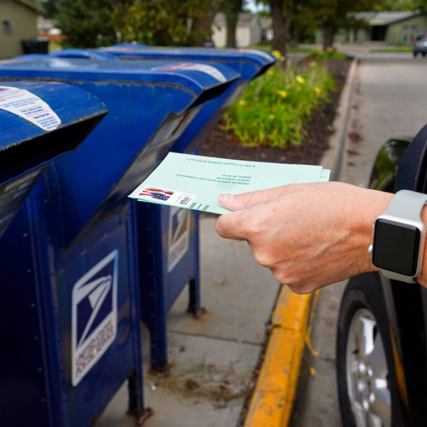 A person drops applications for mail-in-ballots into a mailbox in Omaha, Neb. on Aug. 18, 2020. U.S. Postal Service records show delivery delays have persisted across the country as millions of Americans began voting by mail, raising the possibility of ballots being rejected because they arrive too late. Postal data covering the beginning of October show nearly all of the agency's delivery regions missing agency targets of having more than having more than 95% of first-class mail arrive within five days. (Nati Harnik/Associated Press)