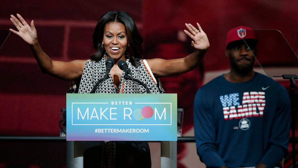 In this Oct. 21, 2015, file photo, former first lady Michelle Obama speaks at the University of Akron as NBA star LeBron James listens in rear, in Akron, Ohio. (AP Photo/Tony Dejak, File)