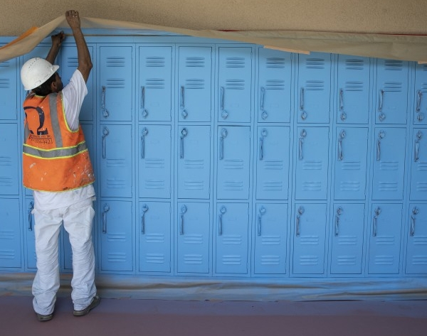 Painting contractor Jose Ortiz tapes a paper mask on along lockers at Oliver Wendell Holmes Middle School in Northridge on Aug. 18, 2020. (Los Angeles Times)
