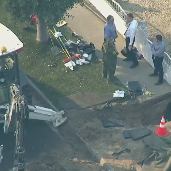 Authorities respond to investigate after human bones were found beneath a sidewalk in Santa Ana on Oct. 27, 2020. (KTLA)