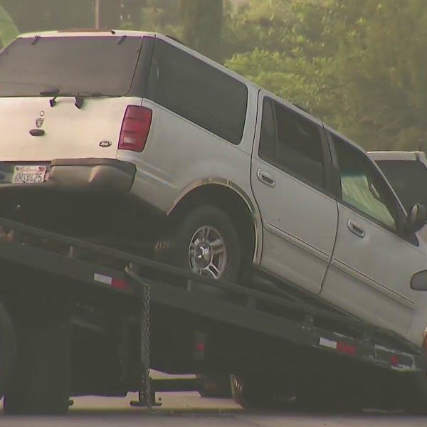 An SUV is removed from the Willowbrook area following an Oct. 4 fatal shooting. (KTLA)