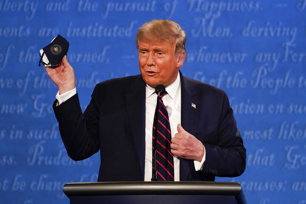 President Trump holds up his face mask during the first presidential debate at Case Western University and Cleveland Clinic, in Cleveland, Ohio. President Trump and first lady Melania Trump have tested positive for the coronavirus, the president tweeted early Friday. (AP Photo/Julio Cortez, File)