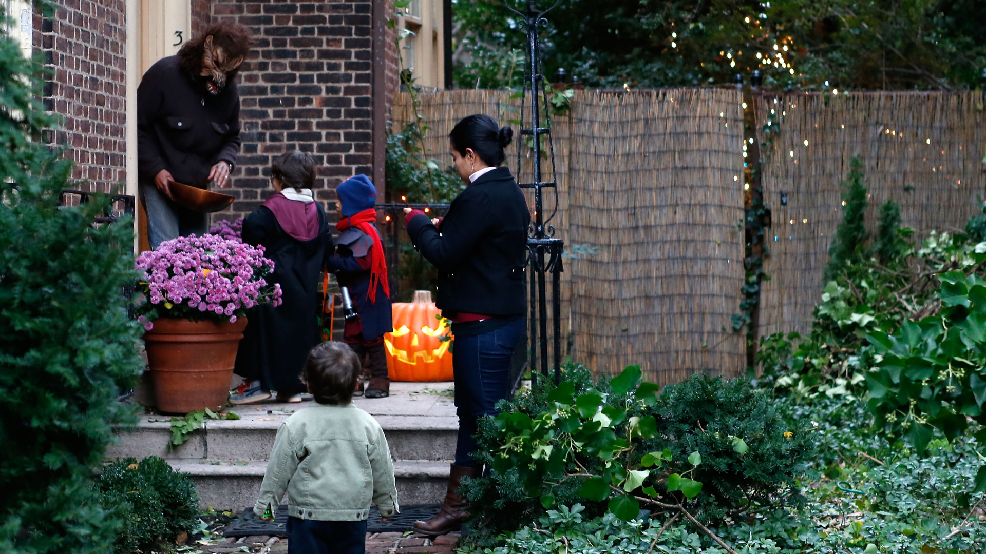 An adult dressed as a werewolf gives candy to trick-or-treating children in Brooklyn, New York City, on Oct. 31, 2012. (Jemal Countess / Getty Images)
