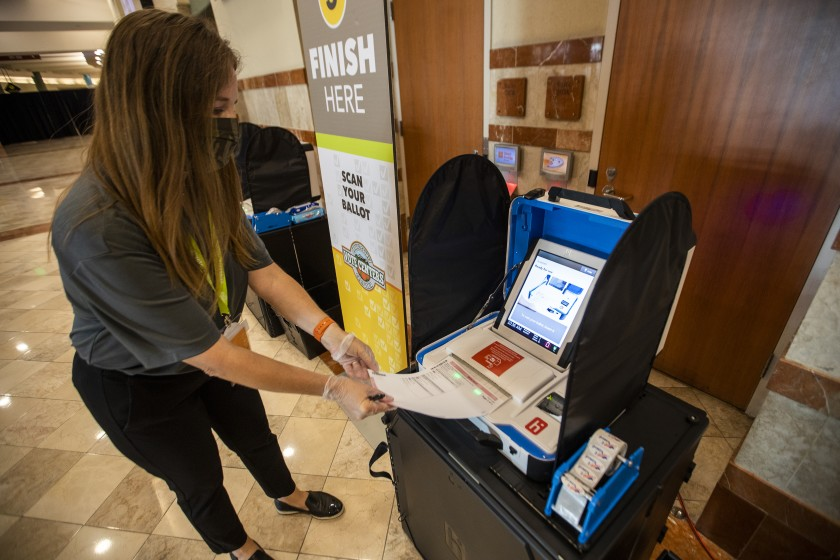 An Orange County election worker demonstrates casting a ballot at the Honda Center in Anaheim, where voters can opt to walk in or drive through starting Oct. 30.(Allen J. Schaben / Los Angeles Times)
