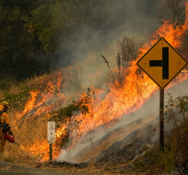 A firefighter uses a drip torch during a backfire operation on Sept. 29, 2020 as the Glass Fire burns along Silverado Trail in Calistoga. (Kent Nishimura / Los Angeles Times)