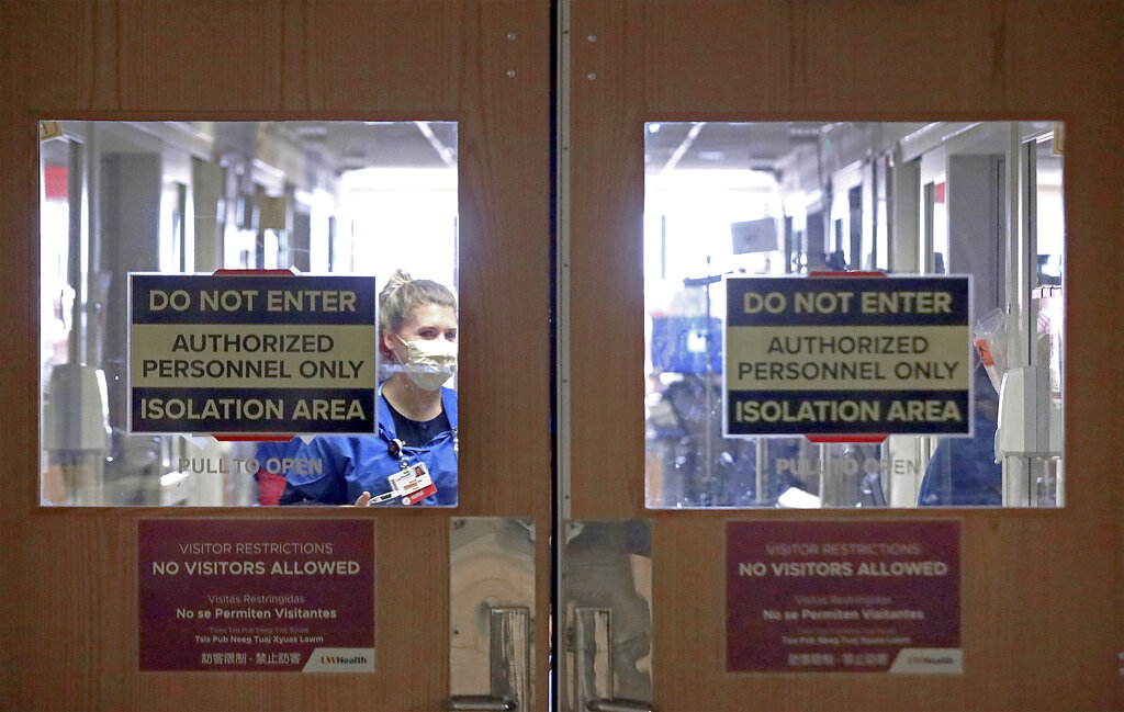 In this Nov. 5, 2020, photo, doors to a COVID-19 treatment unit at UW Health in Madison, Wisconsin, caution hospital personnel and visitors. (John Hart/Wisconsin State Journal via Associated Press)