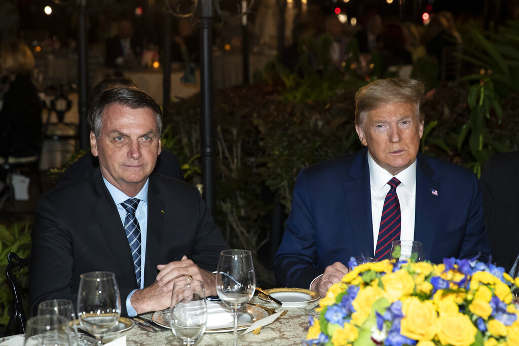 In this March 7, 2020, file photo President Donald Trump is seated before a dinner with Brazilian President Jair Bolsonaro, left, at Mar-a-Lago in Palm Beach, Fla. (AP Photo/Alex Brandon, File)