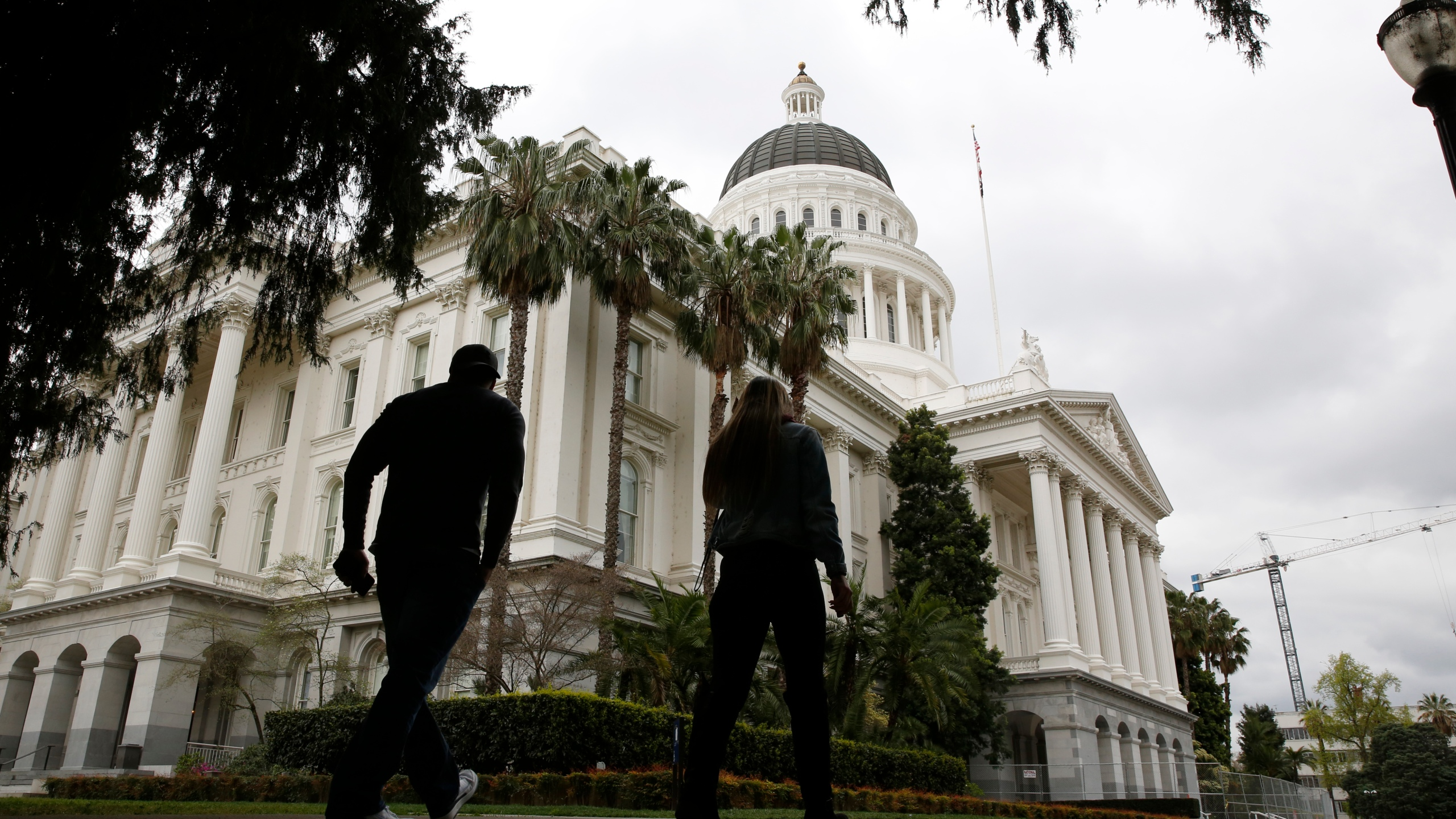 People walk near the state Capitol in Sacramento on March 18, 2020. (Rich Pedroncelli / Associated Press)