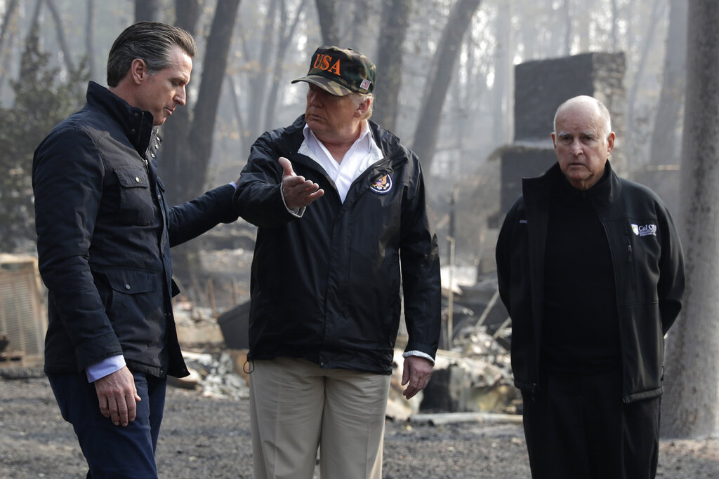President Donald Trump talks with Gov. Gavin Newsom, left, and as then-Gov. Jerry Brown listens during a visit to a neighborhood impacted by the wildfires in Paradise on Nov. 17, 2018. (AP Photo/Evan Vucci, File)