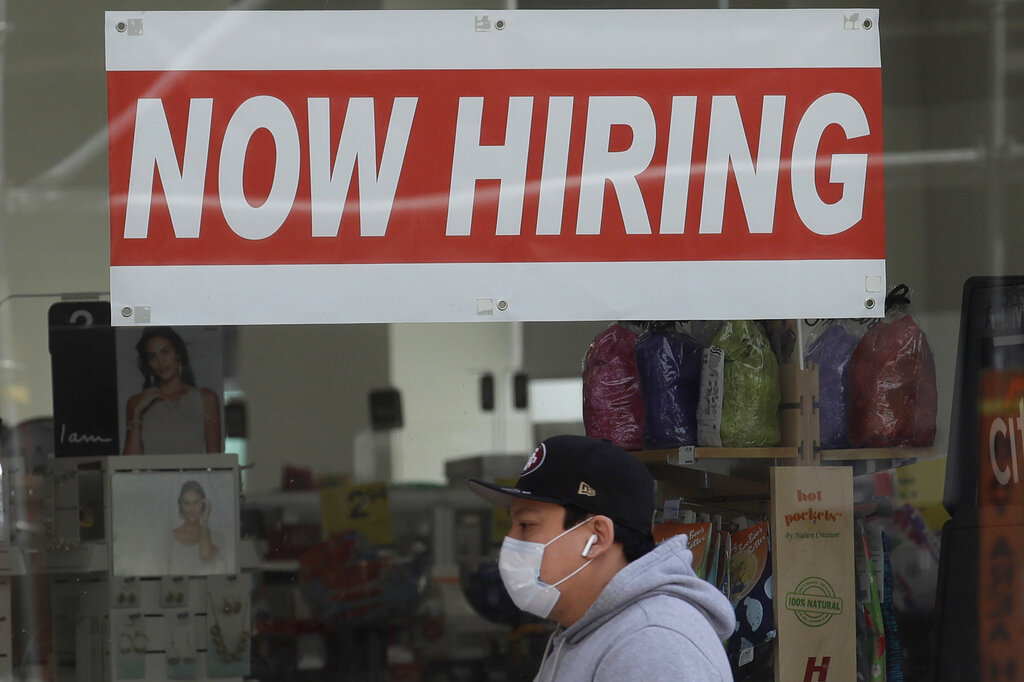This May 7, 2020, file photo shows a man wearing a mask while walking under a Now Hiring sign at a CVS Pharmacy during the coronavirus outbreak in San Francisco. (AP Photo/Jeff Chiu, File)