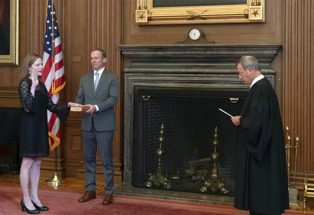 In this image provided by the Collection of the Supreme Court of the United States, Chief Justice John G. Roberts, Jr., right, administers the Judicial Oath to Judge Amy Coney Barrett, Tuesday, Oct. 27, 2020, in Washington. (Fred Schilling/Collection of the Supreme Court of the United States via AP)