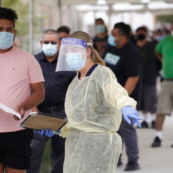 In this July 22, 2020, file photo, people line up behind a health care worker at a mobile coronavirus testing site at the Charles Drew University of Medicine and Science, in Los Angeles. (AP Photo/Marcio Jose Sanchez, File)