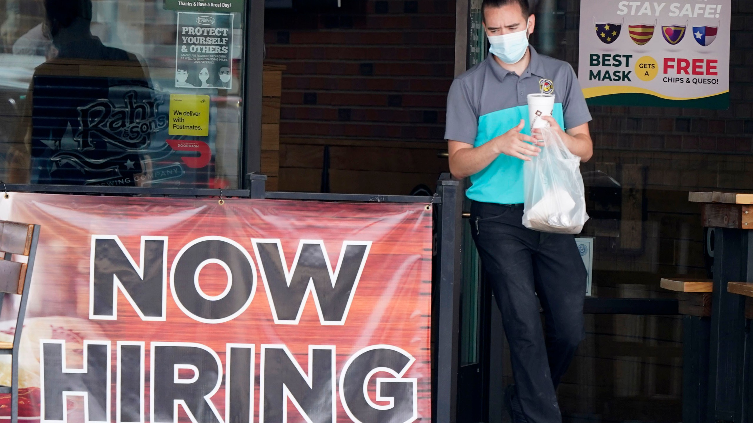 In this Sept. 2, 2020 file photo, a customer wears a face mask as they carry their order past a now hiring sign at an eatery in Richardson, Texas. (AP Photo/LM Otero, File)