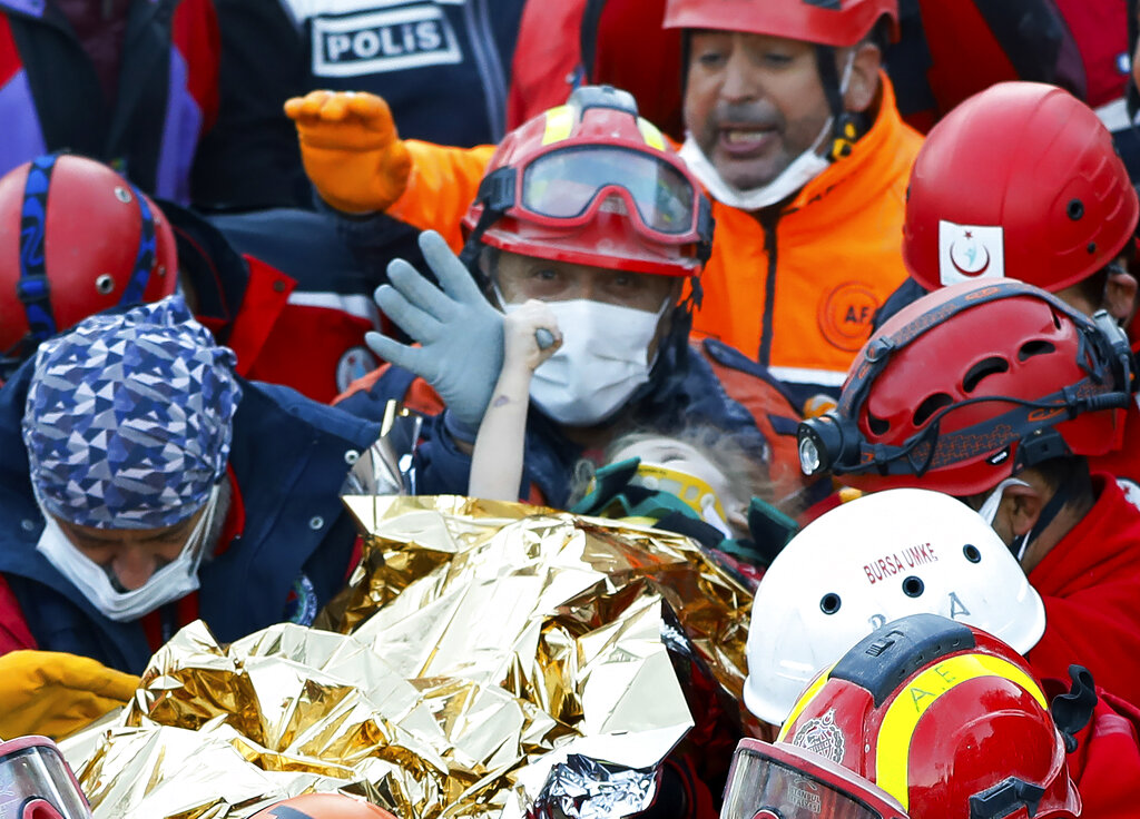 In this handout photo made available by the Istanbul Fire Authority, members of various rescue services carry 3-year-old girl Elif Perincek, after she was rescued from the rubble of a building some 65 hours after a magnitude 6.6 earthquake in Izmir, Turkey on Nov. 2, 2020. (Istanbul Fire Authority via AP)