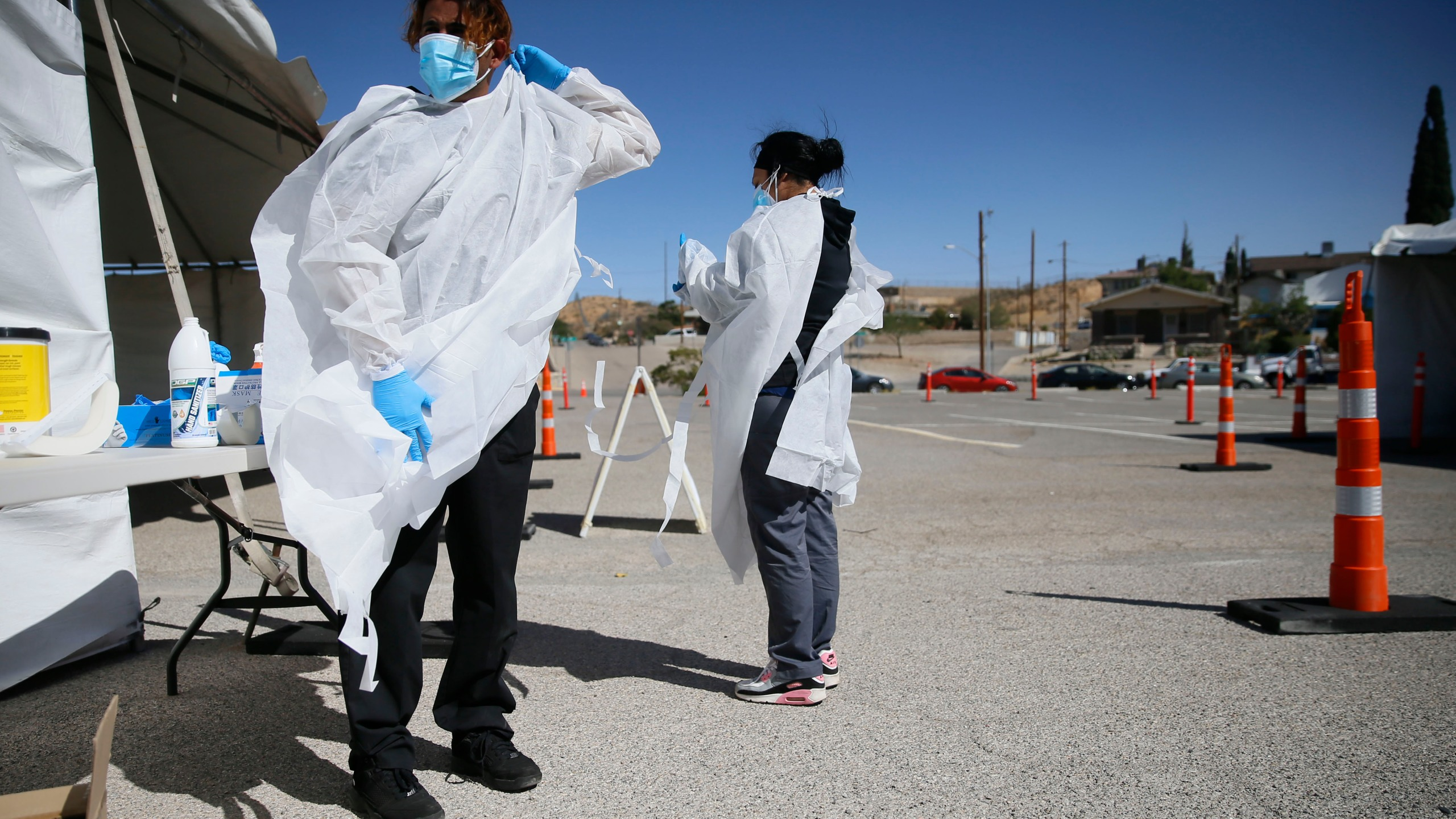 In this Oct. 26, 2020, file photo, Jacob Newberry puts on new PPE at the COVID-19 state drive-thru testing location at UTEP in El Paso, Texas. (Briana Sanchez/The El Paso Times via AP, File)