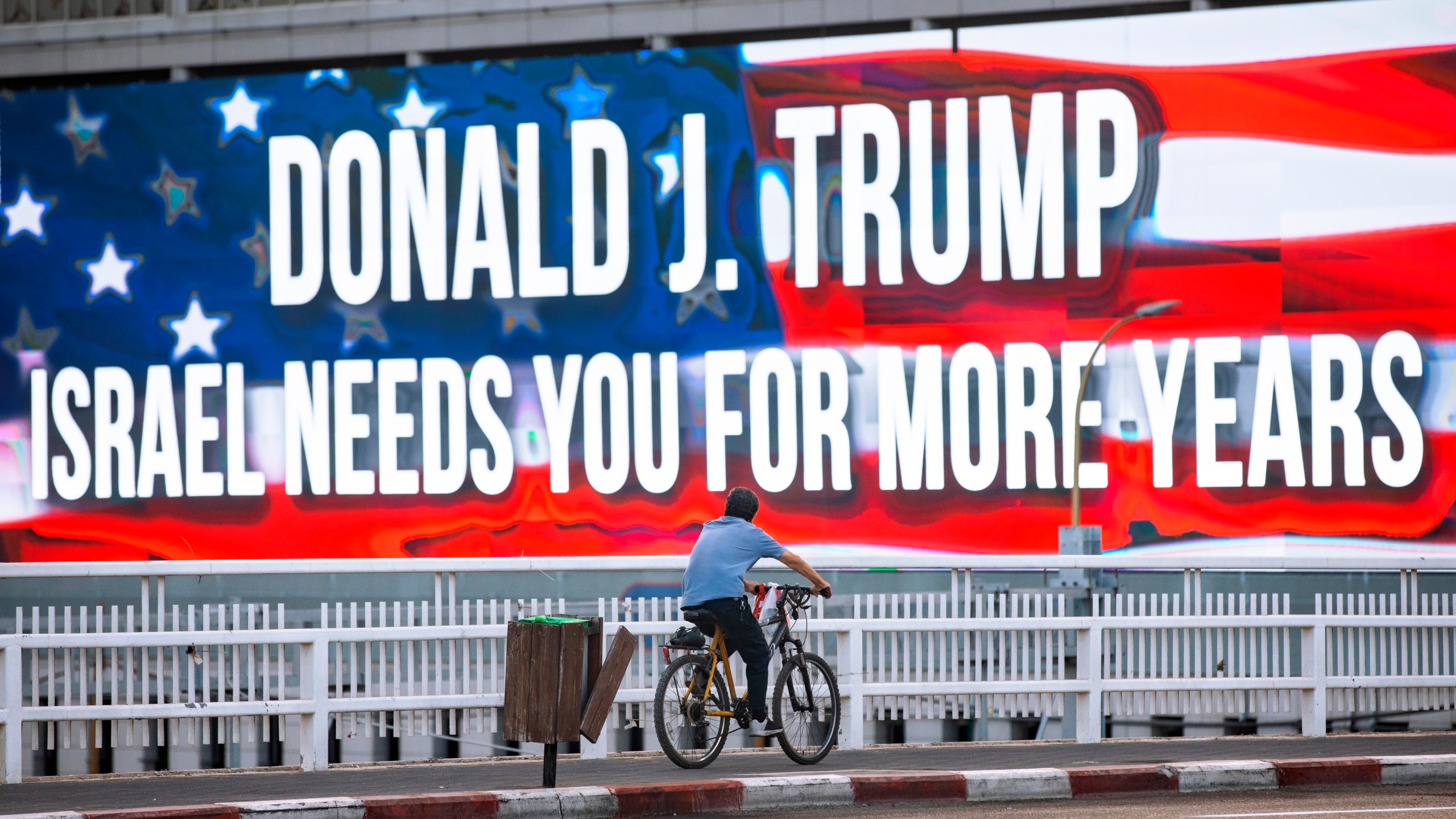 In this Oct. 21, 2020 file photo a cyclist rides next to a billboard supporting President Donald Trump in Tel Aviv ahead of the U.S presidential election. (Oded Balilty/Associated Press)