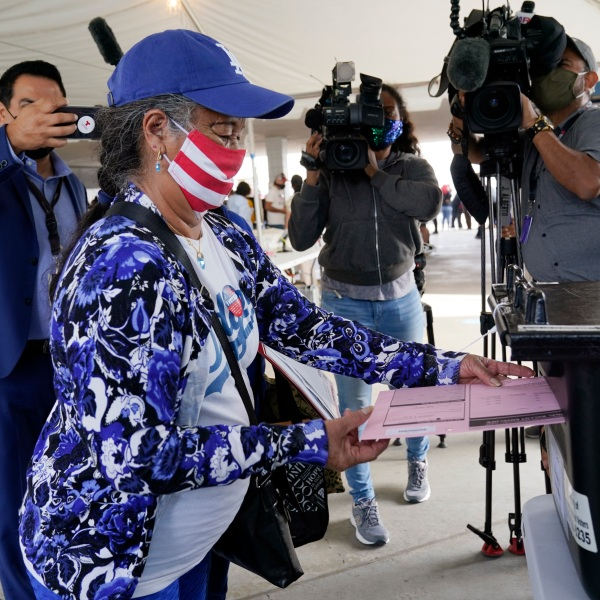First-time voter Salvadora Martir, 73, turns in her ballot on Election Day at Dodger Stadium, Tuesday, Nov. 3, 2020, in Los Angeles. (AP Photo/Chris Pizzello)