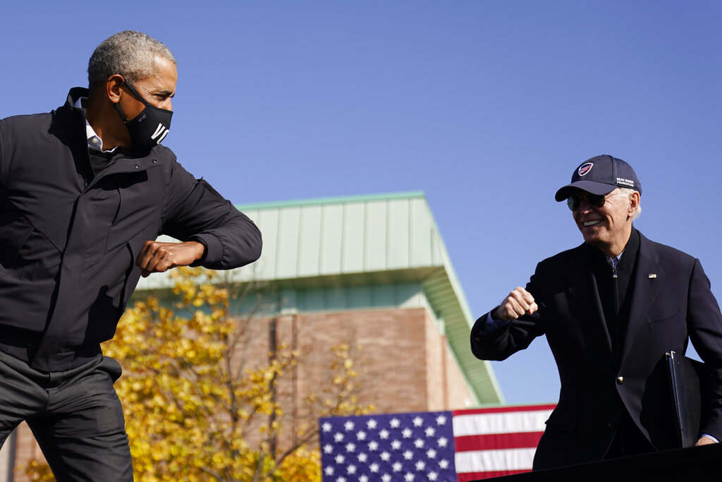 In this Oct. 31, 2020, file photo Democratic presidential candidate former Vice President Joe Biden, right, and former President Barack Obama greet each other with an air elbow bump, at the conclusion of rally at Northwestern High School in Flint, Mich. (AP Photo/Andrew Harnik, File)