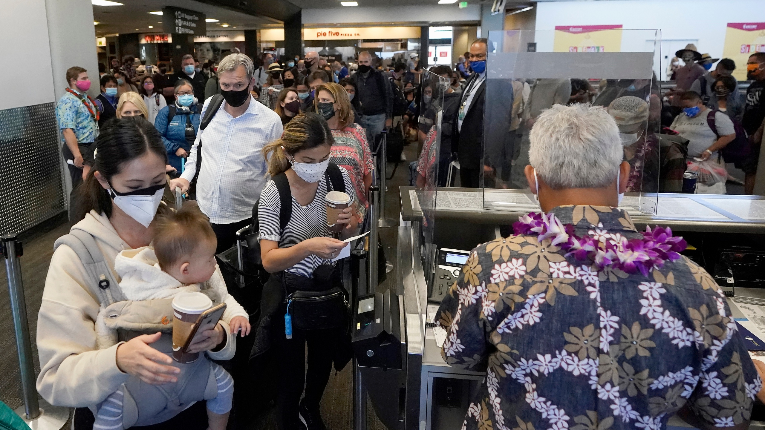 In this Oct. 15, 2020, file photo, United Airlines passengers walk past the gate to board a flight to Hawaii at San Francisco International Airport. (AP Photo/Jeff Chiu, File)