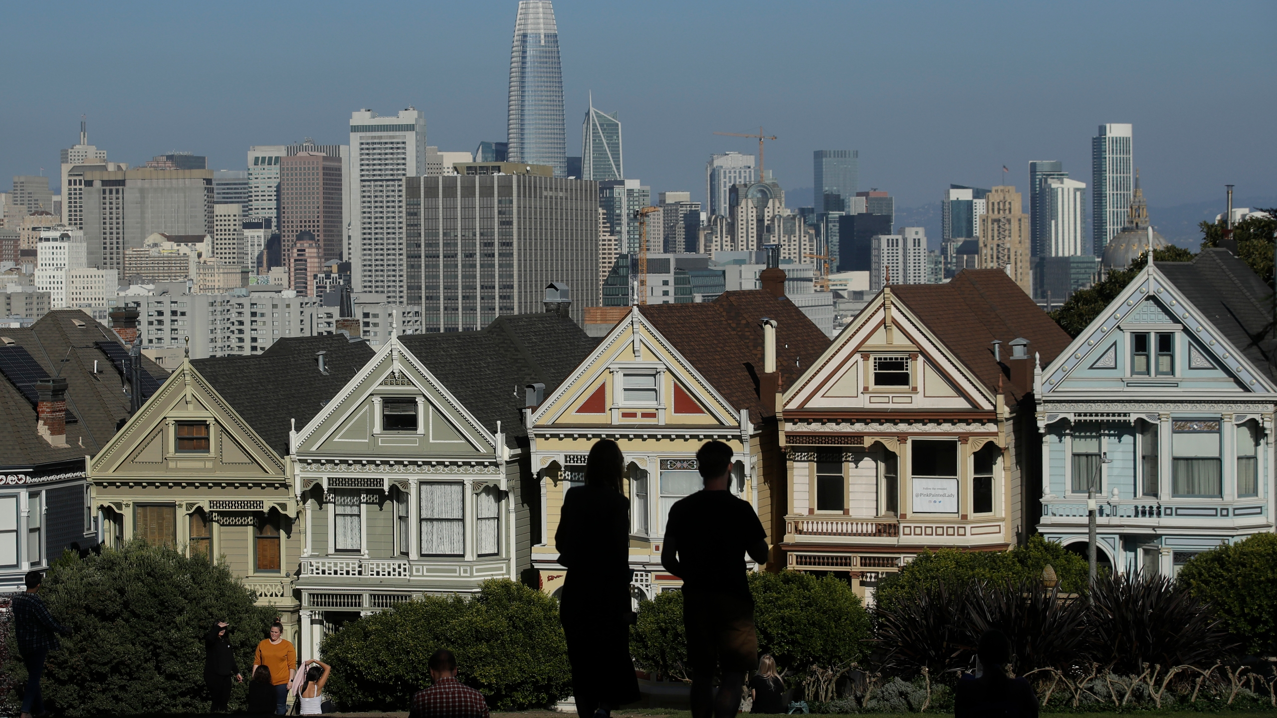 "Visitors look toward the ""Painted Ladies,"" a row of historical Victorian homes, in front of the San Francisco skyline from Alamo Square Park on Feb. 26, 2020. (Jeff Chiu / Associated Press)"
