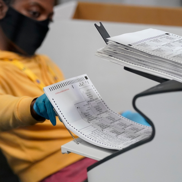 A county election worker scans mail-in ballots at a tabulating area at the Clark County Election Department, Thursday, Nov. 5, 2020, in Las Vegas. (AP Photo/John Locher)