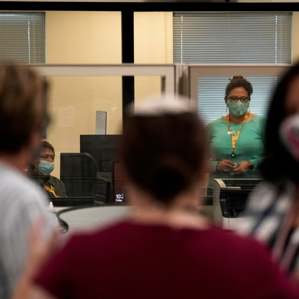 Observers, in foreground, chat as election workers work in a tabulation room at the Clark County Election Department in North Las Vegas on Nov. 6, 2020. (Jae C. Hong / Associated Press)