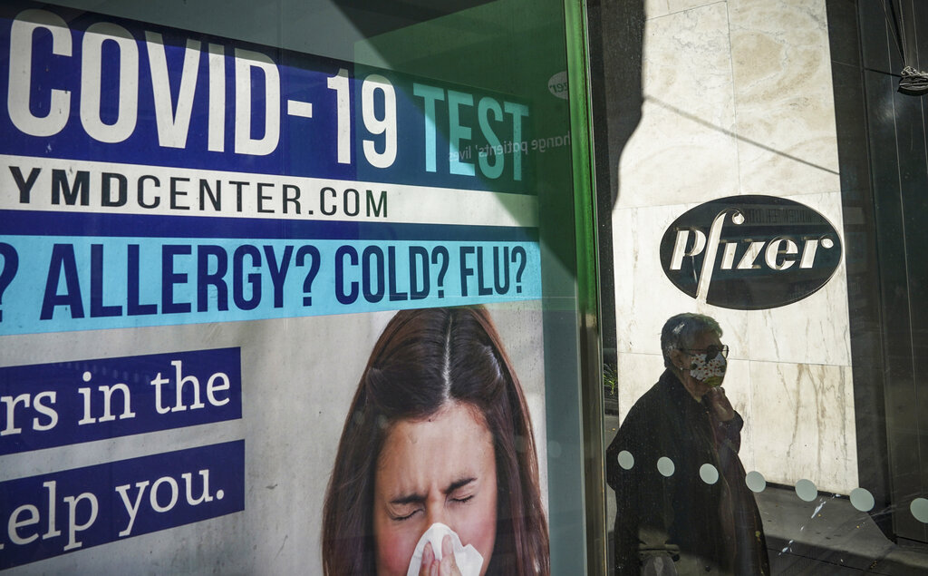 A bus stop ad for COVID-19 testing is shown outside Pfizer world headquarters in New York on Nov. 9, 2020.(AP Photo/Bebeto Matthews)