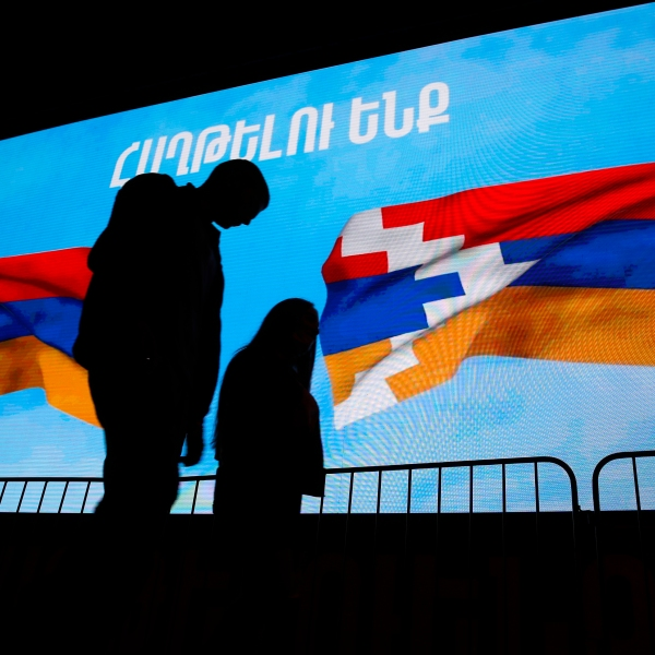 "A couple walk past a screen displayed Armenian, left, and Nagorno-Karabakh's flags with sign reading ""We will win"" in Yerevan, the capital of Armenia on Nov. 9, 2020. (Associated Press)"