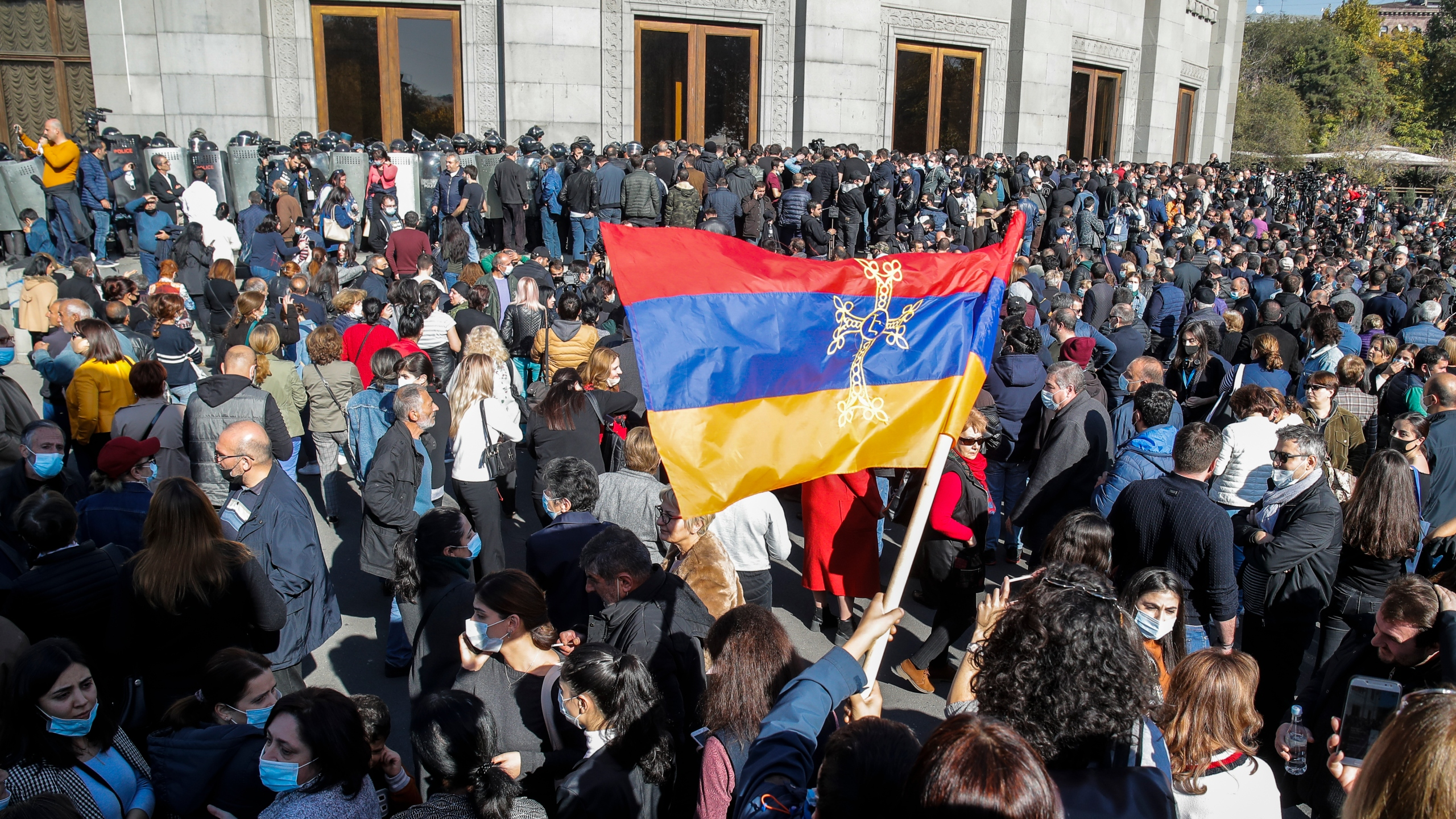 Protesters wave an Armenian national flag during a protest against an agreement to halt fighting over the Nagorno-Karabakh region, in Yerevan, Armenia, Wednesday, Nov. 11, 2020. (AP Photo/Dmitri Lovetsky)