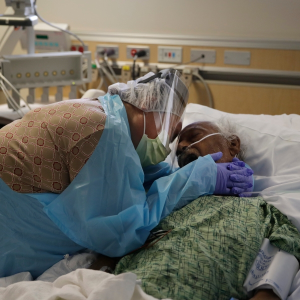 In this July 31, 2020, file photo, Romelia Navarro, 64, weeps while hugging her husband, Antonio, in his final moments in a COVID-19 unit at St. Jude Medical Center in Fullerton. (Jae C. Hong / Associated Press)